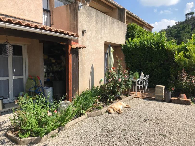 Maison côté sud. Devant la cuisine, plate-bandes de rosiers, iris, menthe. Terrasse et mobilier d'extérieur.