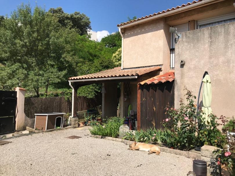 Maison côté sud. Gravier, plate-bandes de rosiers, iris, menthe. Le long de la clôture, la niche de Gizmo.