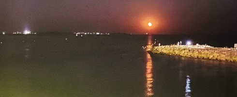 red moon rising above the sea